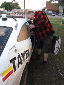 Service crew member Kevin Wilson fixing Mike Ward's window after he hit a tree.