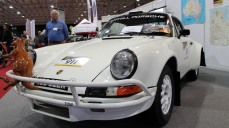 """White Porsche rally car with a """"for sale"""" sign"""