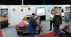 The COT stand at Race Retro with visitors talking to Ian