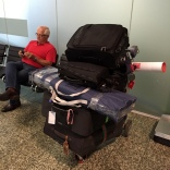 A big pile of luggage at the airport, ready for check-in.