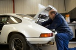 Francis Tuthill working on a white Porsche.