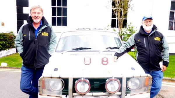 John Henderson and jeff West standing next to their car in England