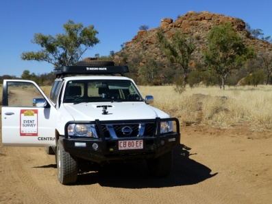Survey car in front of a rocky outcrop.