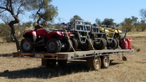 A trailer arrying four quads.
