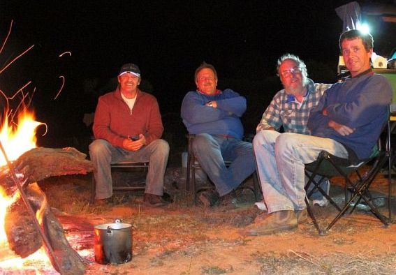 Crew around a campfire.